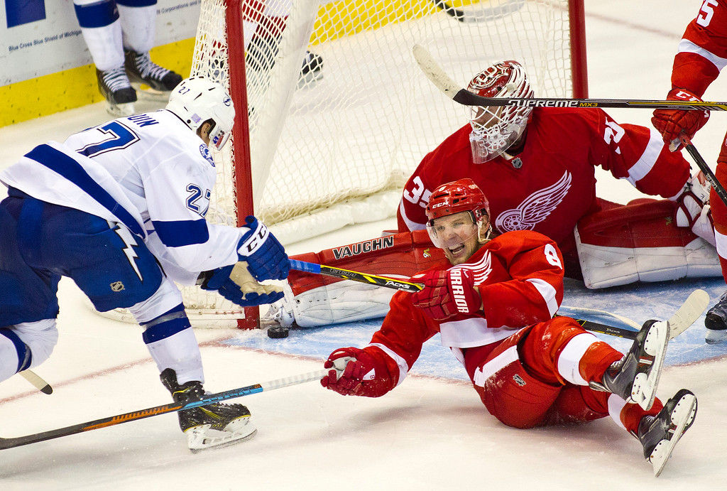. Tampa Bay Lightning forward Jonathan Drouin (27) gets his stick tangled with Detroit Red Wings forward Justin Abdelkader (8), as his shot is blocked by goalie Jimmy Howard (35), during overtime of an NHL hockey game in Detroit, Mich., Sunday, Nov. 9, 2014. Tampa Bay won 4-3 in shootouts. (AP Photo/Tony Ding)