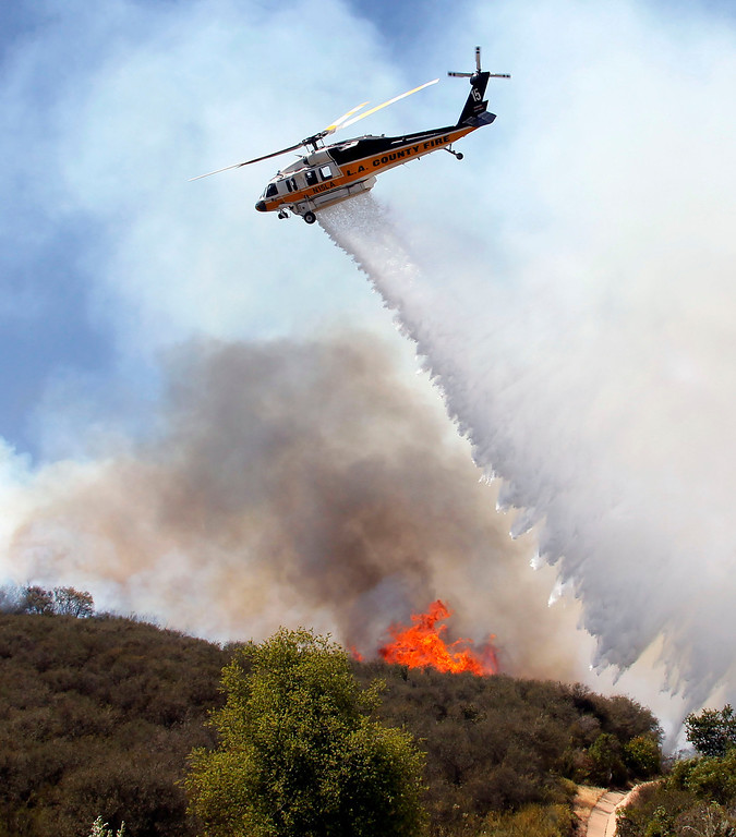 . A helicopter drops water on a hotspot over a hill near Thousand Oaks, Calif. on Thursday, May 2, 2013.  (AP Photo/Nick Ut)