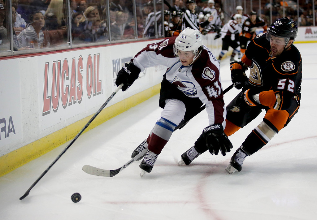 . Colorado Avalanche center Michael Sgarbossa, left, battles Anaheim Ducks defenseman Brendan Bell for the puck during the first period of an NHL hockey preseason game in Anaheim, Calif., Monday, Sept. 22, 2014. (AP Photo/Chris Carlson)