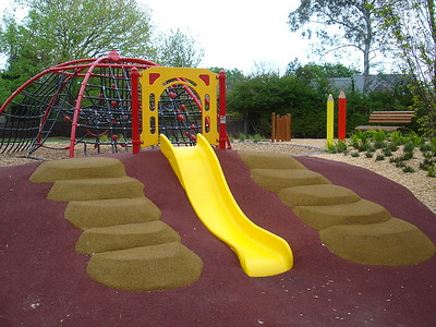 single yellow plastic slide on mound with softfall rubber and moulded boulders for clambering