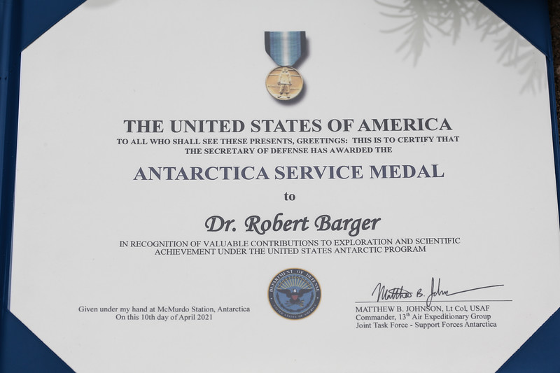 Dr. Robert N. Barger was presented the Antarctica Service Medal by CAP National Vice Commander Brig. Gen. Edward Phelka on May 15, 2021, in South Bend, Indiana. As a 17-year-old Cadet Major in the Civil Air Patrol, Cadet Barger was selected as the official CAP participant in Operation Deep Freeze II.  Operation Deep Freeze II was a year-long US-Navy led operation to Antarctica and the South Pole where Cadet Barger would serve as a working member of the 80-person team operating the C-124 Globemaster.  From October 1956 until February 1957, Dr. Barger managed to: Be a crewmember of the first US Air Force aircraft to fly over the south pole, Be the first teenager to fly over the south pole, Be the first person to celebrate an 18th birthday in Antarctica, Be the first Catholic to serve as an altar boy in Antarctica.   Dr. & Mrs. Barger, his niece Clare Libbing, Rev. Paul Doyle, C.S.C. and Brig. Gen Edward Phelka (U.S. Air Force Auxiliary photo by Lt. Col. Robert Bowden)