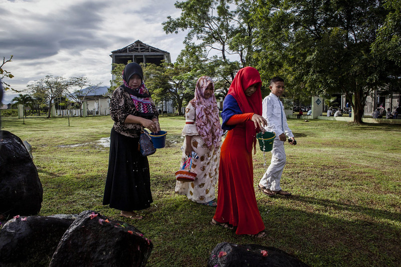 . An Acehnese family pours water as they pray at mass grave to commemorate the tenth anniversary of the Boxing Day tsunami on December 26, 2014 in Banda Aceh, Indonesia. Aceh was the worst hit location, being the closest major city to the epicenter of the 9.1 magnitude quake, suffering a huge hit from the following tsunami and resulting in around 130,000 deaths. Throughout the affected region of eleven countries, nearly 230,000 people were killed, making it one of the deadliest natural disasters in recorded history. (Photo by Ulet Ifansasti/Getty Images)
