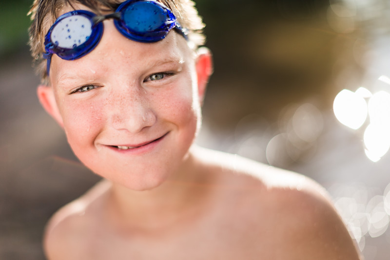 A young boy swimming at the lake.
