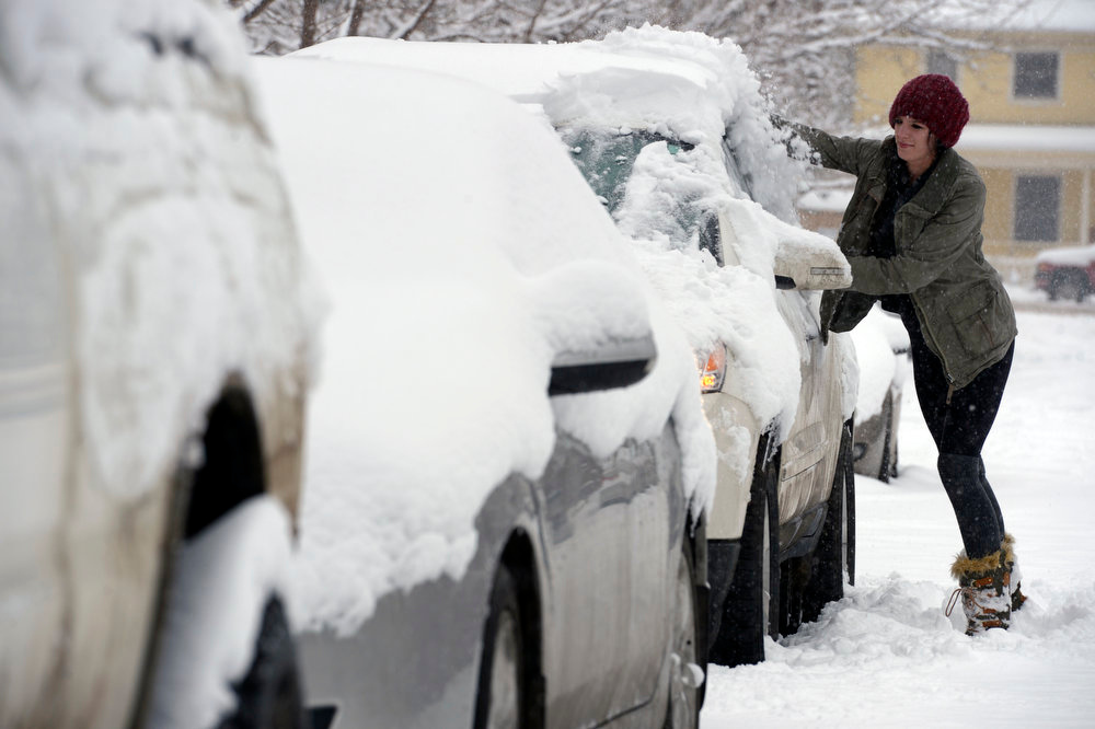. Kirstin Wagner of Boulder clears snow off her car on Mapleton street in Boulder, Co.  A big winter storm hit the metro area leaving well over 6 inches of snow and bringing with it wind and cold temperatures in Boulder, Co on February 24, 2013.    (Photo by Helen H. Richardson/ The Denver Post)