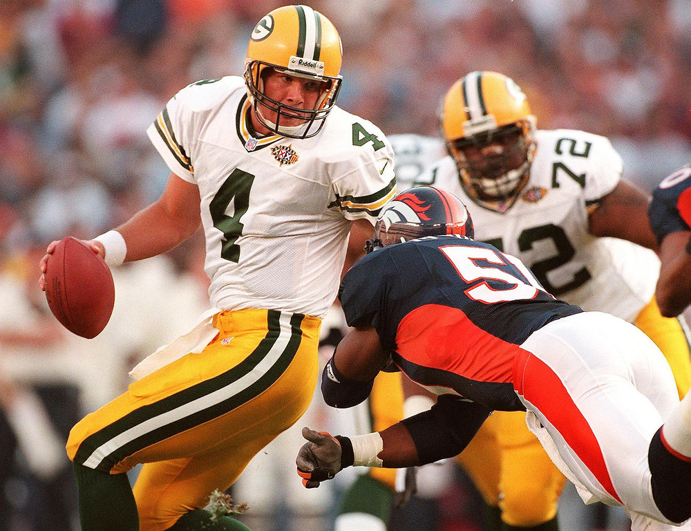 . Green Bay Packers quarterback Brett Favre (L) avoids the rush by Denver Broncos defender John Mobley (R) in the first half of Super Bowl XXXII at Qualcomm Stadium in San Diego, CA 25 January. In the background is Earl Dotson of the Green Bay Packers.   (DON EMMERT/AFP/Getty Images)