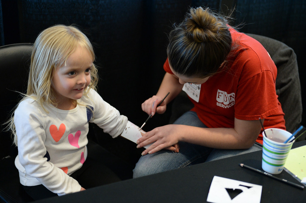 . Peyton Taylor, 4, gets some Avalanche arm paint from Marissa Antola before the game.  (Photo by Karl Gehring/The Denver Post)