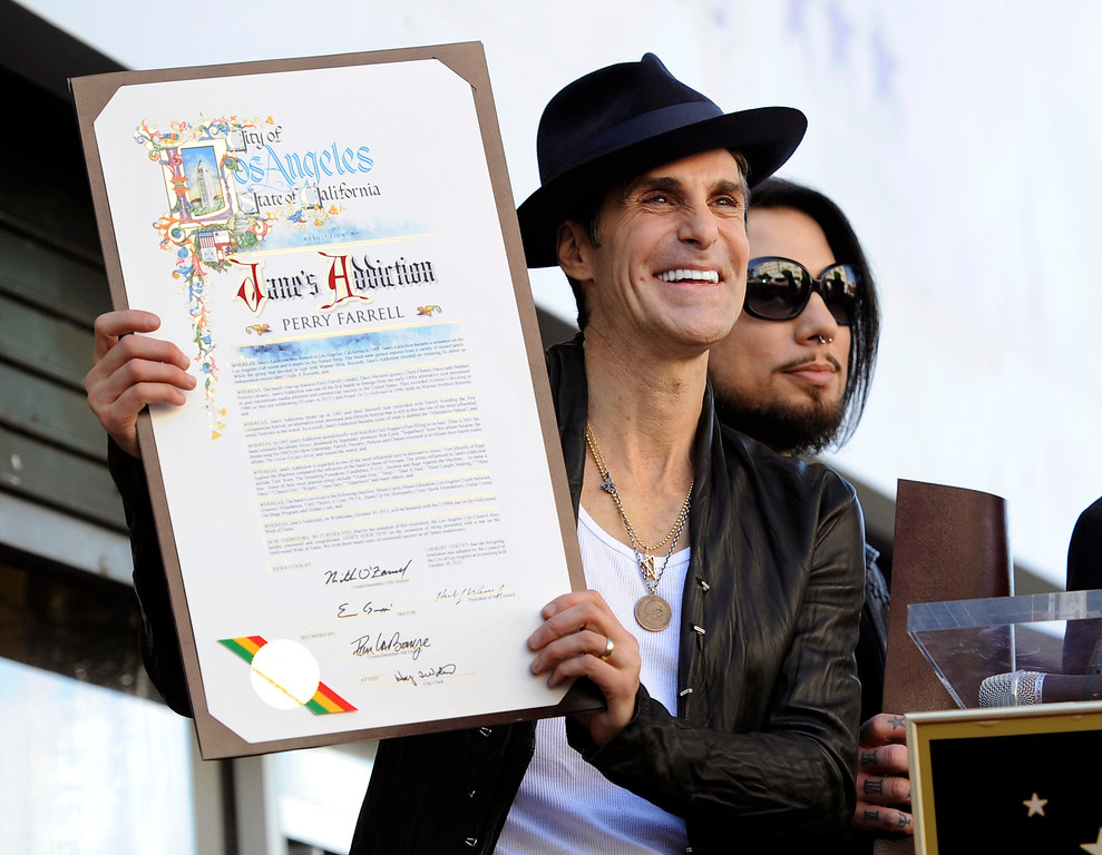 . Perry Farrell, lead singer of Jane\'s Addiction, holds a proclamation from the City of Los Angeles as fellow band member Dave Navarro looks on during a ceremony to award the band a star on the Hollywood Walk of Fame on Wednesday, Oct. 30, 2013 in Los Angeles. (Photo by Chris Pizzello/Invision/AP)