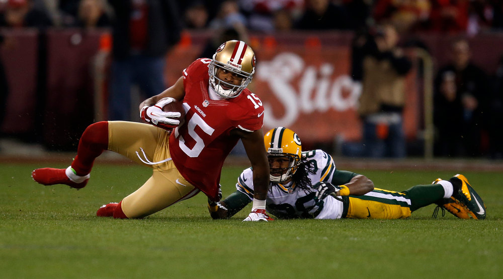Description of . San Francisco 49ers wide receiver Michael Crabtree (15) is pulled down after a catch against the Green Bay Packers' Tramon Williams (38) in the first quarter in the NFC Divisional Playoff on Saturday, January 12, 2013, at Candlestick Park in San Francisco, California. (Nhat V. Meyer/San Jose Mercury News)