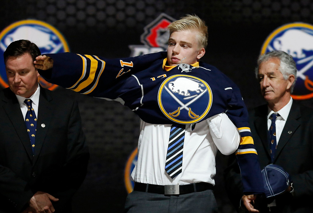 . Rasmus Ristolainen puts on a Buffalo Sabres jersey after being selected by the Sabres as the eighth overall pick in the 2013 National Hockey league (NHL) draft in Newark, New Jersey, June 30, 2013. REUTERS/Brendan McDermid