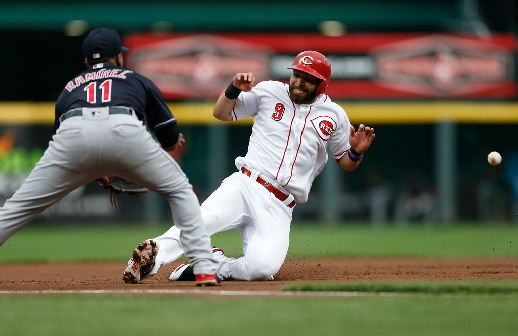 . Cincinnati Reds\' Jose Peraza (9) slides safely into third, advancing on a fly out by Joey Votto, as Cleveland Indians third baseman Jose Ramirez (11) waits for the throw during the first inning of a baseball game Wednesday, Aug. 15, 2018, in Cincinnati. (AP Photo/Gary Landers)