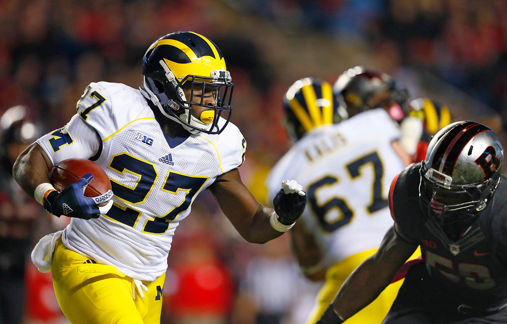 . Michigan running back Derrick Green (27) is pursued by Rutgers\' Quentin Gause during the second half of an NCAA college football game Saturday, Oct. 4, 2014, in Piscataway, N.J. Rutgers defeated Michigan 26-24. (AP Photo/Rich Schultz)
