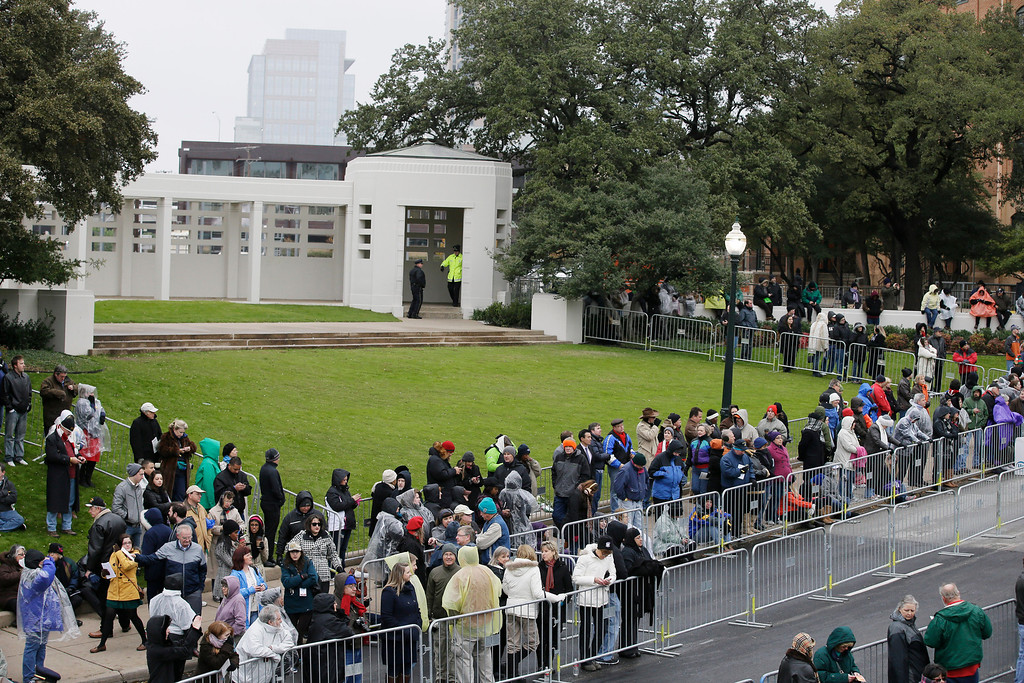 . A crowd gathers on the grassy knoll before a ceremony to mark the 50th anniversary of the assassination of John F. Kennedy, Friday, Nov. 22, 2013, at Dealey Plaza in Dallas. President Kennedy\'s motorcade was passing through Dealey Plaza when shots rang out on Nov. 22, 1963. (AP Photo/Tony Gutierrez)