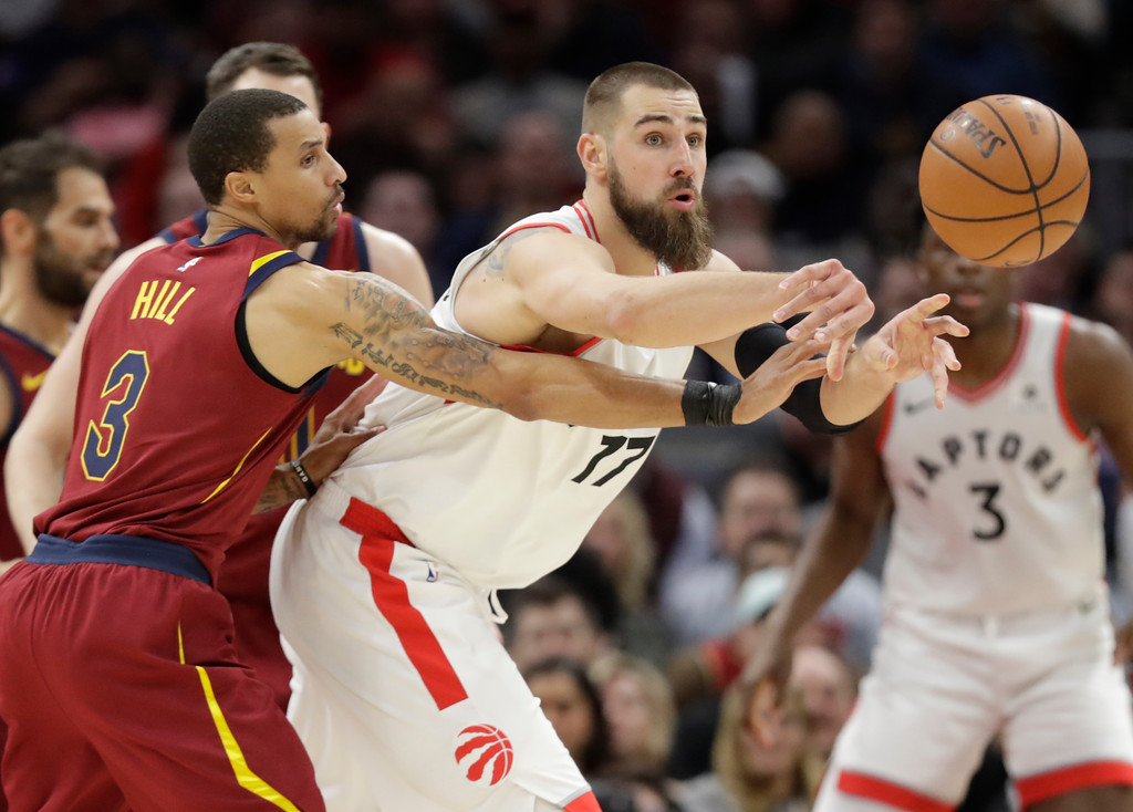 . Toronto Raptors\' Jonas Valanciunas (17), from Lithuania, passes against Cleveland Cavaliers\' George Hill (3) in the second half of an NBA basketball game, Wednesday, March 21, 2018, in Cleveland. (AP Photo/Tony Dejak)