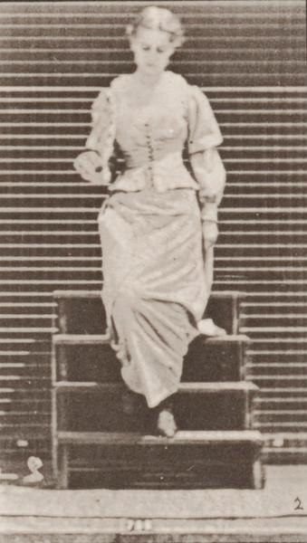 Woman descending stairs, turning and flirting a fan