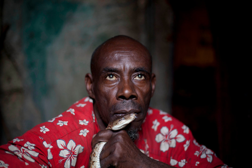. In this Jan. 25, 2013 photo, snake handler Saintilus Resilus holds a snake in front of his lips as he trains the snake to recognize his smell as he prepares for his street performances during the pre-Lenten Carnival season, at his home in Petionville, Haiti. Resilus sees himself as something of a performance artist, showing off with snakes and other animals that Haitians don\'t see every day, earning tips from impromptu audiences. (AP Photo/Dieu Nalio Chery)