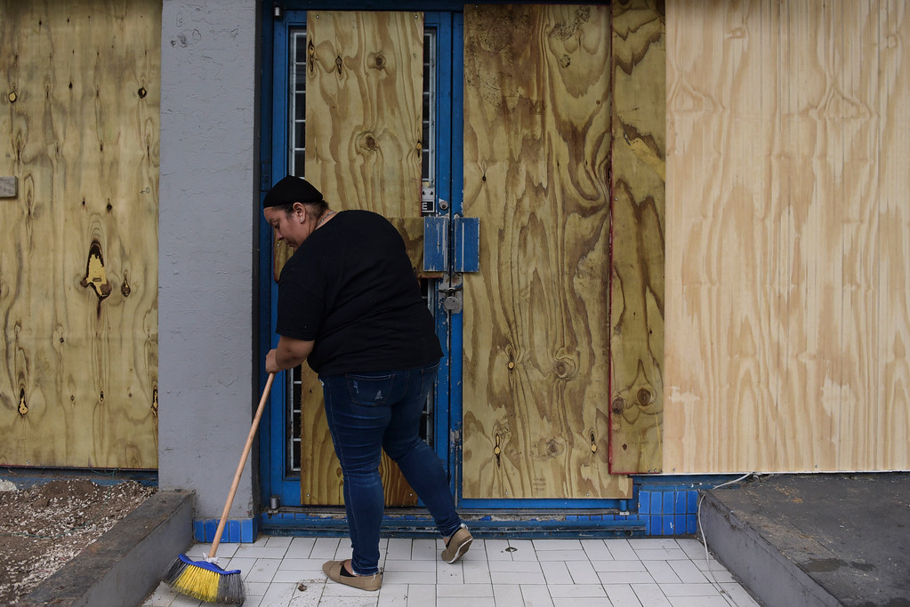 . A woman sweeps the front of a storefront boarded up in preparation for Hurricane Maria, in Humacao, Puerto Rico, Tuesday, Sept. 19, 2017. Puerto Rico is likely to take a direct hit by the category 5 hurricane. Authorities warned people who live in wooden or flimsy homes should find safe shelter before the storm\'s expected arrival on Wednesday. (AP Photo/Carlos Giusti)