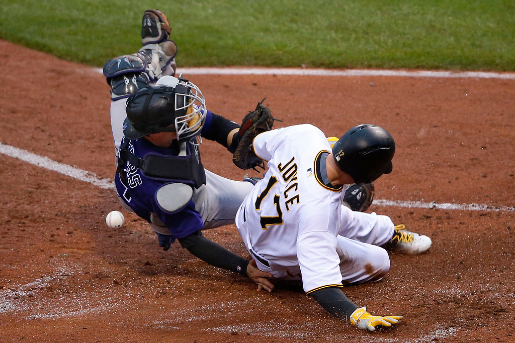 . Pittsburgh Pirates\' Matt Joyce (17) scores on a single by Pirates Jordy Mercer when Colorado Rockies catcher Tony Wolters can\'t handle the relay throw from center field during the fourth inning of a baseball game in Pittsburgh, Saturday, May 21, 2016. (AP Photo/Gene J. Puskar)