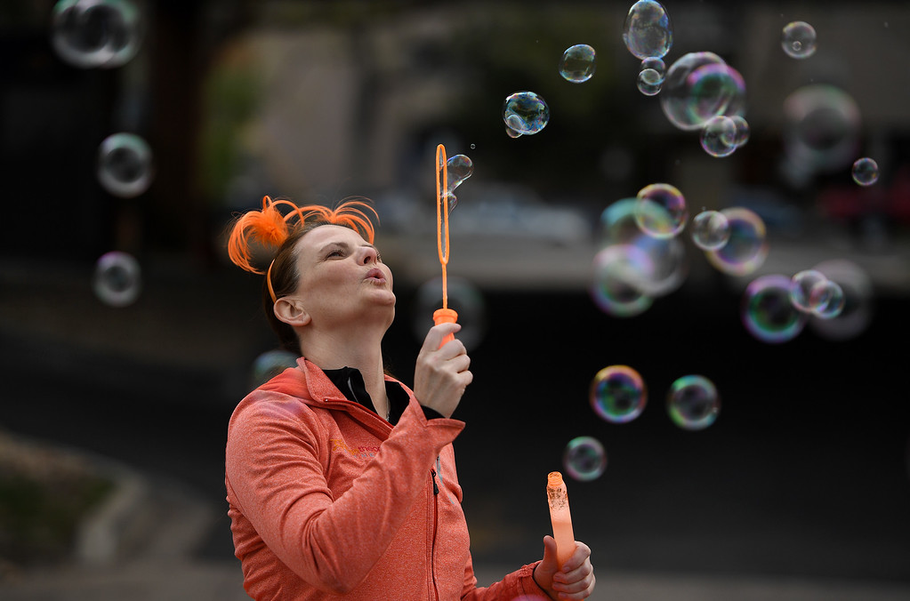 . DENVER, CO - APRIL 24:  Stacie Knapp blows bubbles along Steele Street at the start of the 10 mile race of the 34th annual Cherry Creek Sneak road races on April 24, 2016 in Denver, Colorado. The day\'s races included a 10 miler, a 1.5 mile Sneak Sprint, a 5K and a 5 mile run and walk.   (Photo by Helen H. Richardson/The Denver Post)