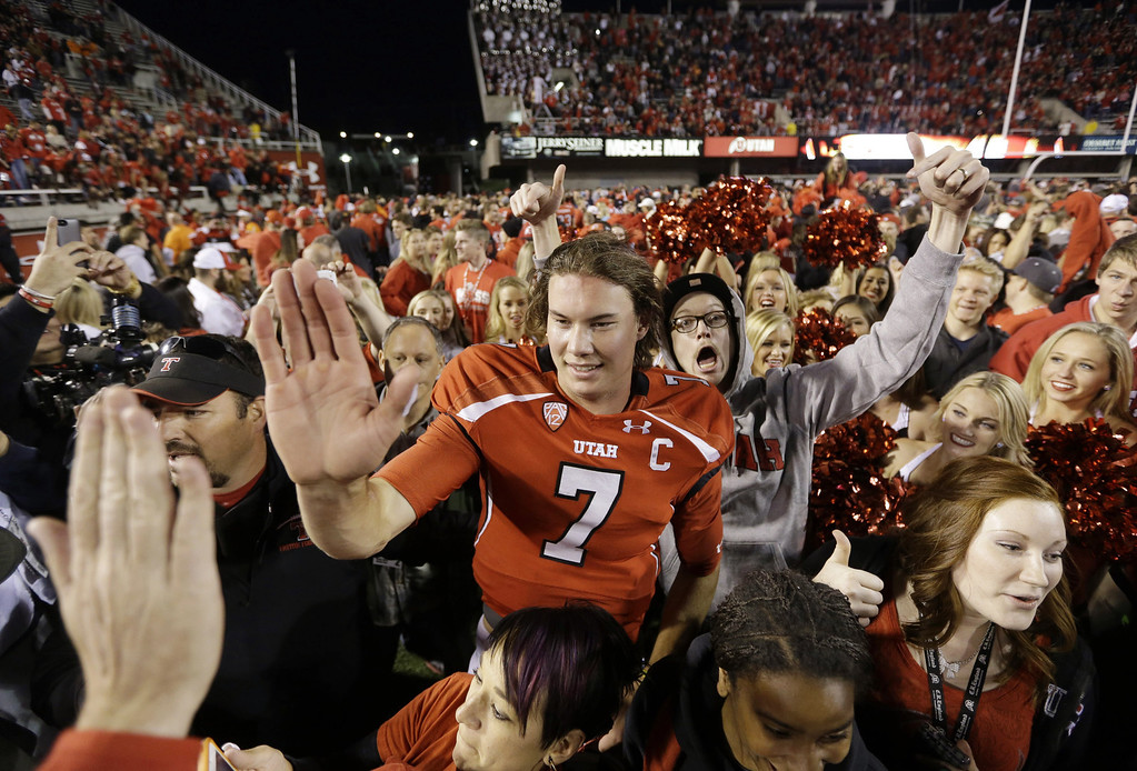 . Utah quarterback Travis Wilson (7) receives high-fives a fan after Utah defeated Stanford 27-21 during an NCAA college football game on Saturday, Oct. 12, 2013, in Salt Lake City. (AP Photo/Rick Bowmer)
