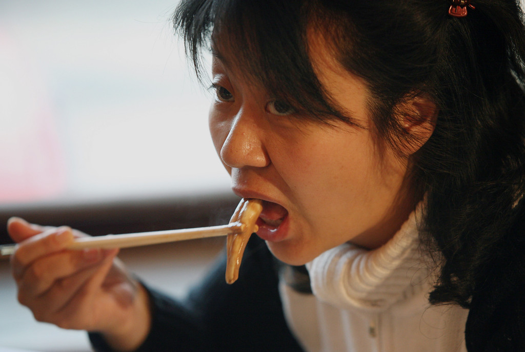 ". A Chinese woman eats from an ox and dog penis dish at the Guolizhuang ""strength in the pot\"" penis restaurant in China\'s capital Beijing March 3, 2006. The restaurant offers more than 30 types of animal penises served in a Chinese hotpot style. According to the theory of traditional Chinese medicine, the penis of certain animals is full of nutrients which brings men energy. And because it contains gelatine albumen, it is said to have excellent cosmetic effects for women, especially beneficial for the skin. REUTERS/Reinhard Krause"
