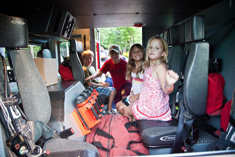 Children check out the back seats of the firetruck.