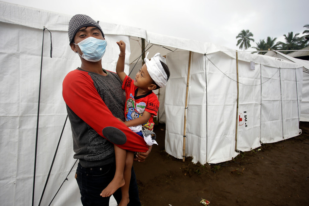. A father holds his son at an evacuated area in Karangasem, Indonesia, Monday, Nov. 27, 2017. Indonesian authorities ordered a mass evacuation of people Monday from an expanded danger zone around an erupting volcano on Bali that has forced the island\'s international airport to close, stranding tens of thousands of travelers. (AP Photo/Firdia Lisnawati)