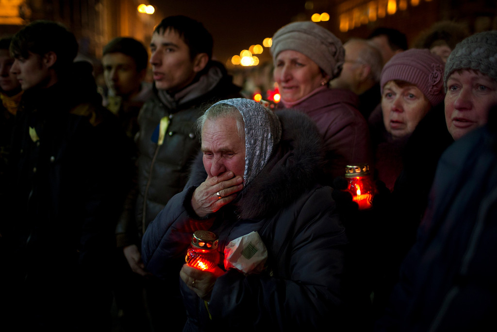 . People react during the funeral of anti-Yanukovych protester Bailuk Alexander, 40, killed in a recent clash with riot police in Kiev\'s Independence Square, Ukraine, Friday, Feb. 28, 2014. (AP Photo/Emilio Morenatti)