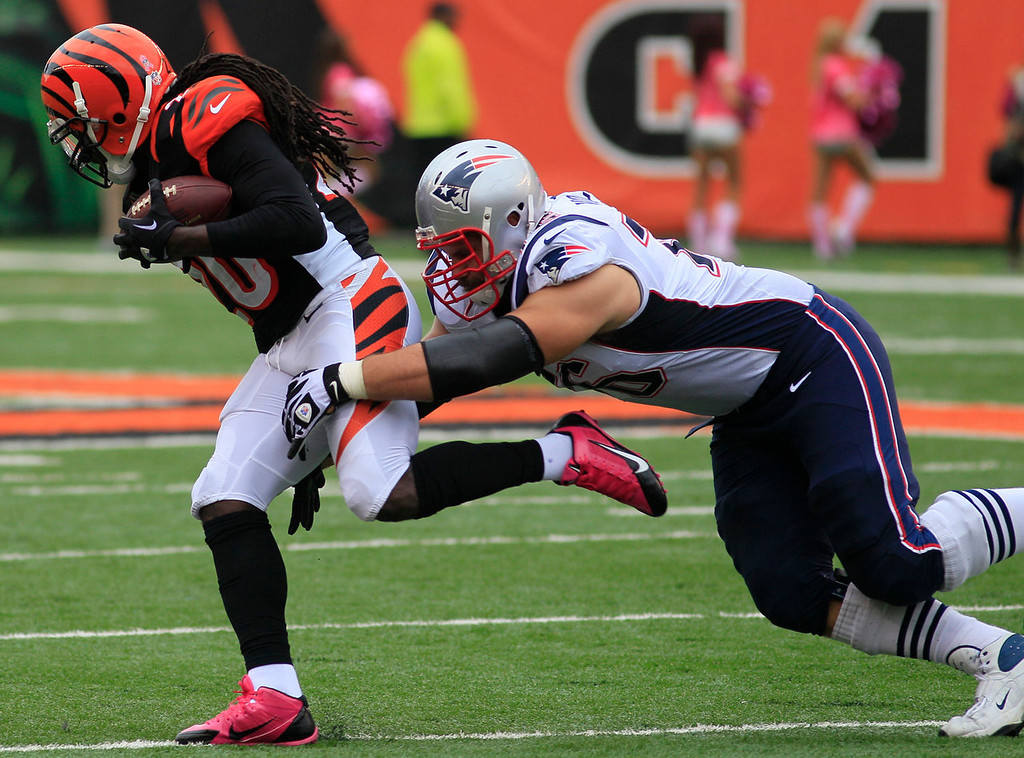 . Cincinnati Bengals free safety Reggie Nelson is tackled by New England Patriots tackle Sebastian Vollmer, right, after recovering a fumble in the first half of an NFL football game on Sunday, Oct. 6, 2013, in Cincinnati. (AP Photo/Tom Uhlman)