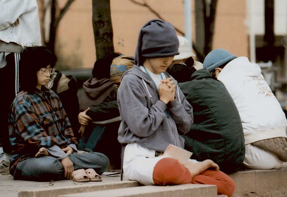 . Followers of the religious sect Aum Supreme Truth pray outside its property in Osaka on March 24, 1995 after police moved them out during a raid. Shoko Asahara, the head of the group, has denied any link with the nerve-gas assault on the Tokyo subway on March 20th that killed 12 people and left more than 5,500 injured. JIJI PRESS/AFP/Getty Images