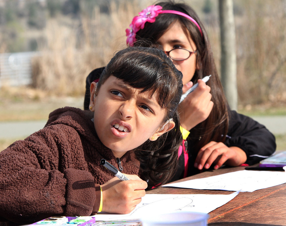. Noora Amana, 8, left, and Azalia Quintero, 9, from Franklin Elementary School in Oakland, work on watercolor pictures of trout as part of the Trout in the Classroom program sponsored by the State Department of Fish and Wildlife at Shadow Cliffs Regional Recreation Area in Pleasanton, Calif., on Thursday, March 14, 2013. Classes are given 35 trout eggs and tanks. When the hatchlings are large enough they are released into local lakes.  About 200 students and teachers released fish.  (Jim Stevens/Staff)