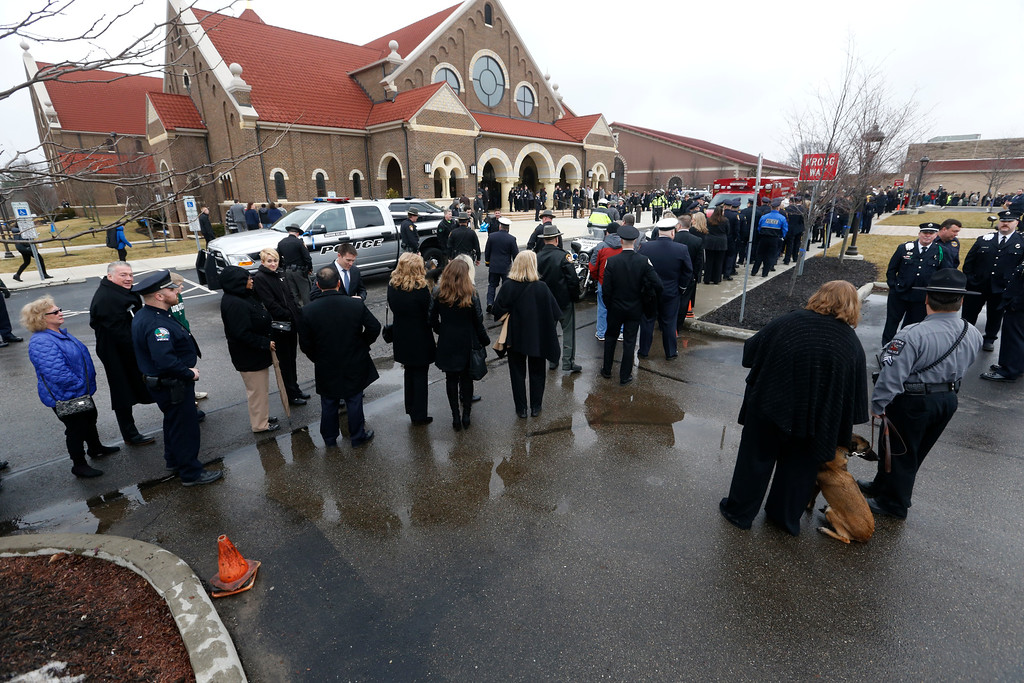 . Mourners line up outside St. Paul the Apostle Catholic Church in Westerville, Ohio, during the public viewing and before funeral services for Westerville police officers Anthony Morelli and Eric Joering Friday, Feb. 16, 2018. The two veteran officers were shot after entering a residence on Saturday. The officers returned fire, wounding 30-year-old Quentin Smith, who has been charged with aggravated murder and remains hospitalized. (AP Photo/Paul Vernon)