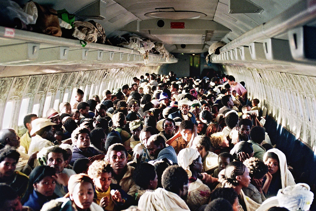""". ON BOARD OF ISRAELI PLANE:Ethiopian Jews known as \""""Falashas\"""" sit on bard of an Israeli Air Force Boeing 707, during t heir transfer from Addis Ababa to Tel Aviv early 25 1991. Sixteen thousand five hundred \""""Falashas\"""" were evacuated from Ethiopia as part of \""""Operation Solomon\"""", the world\'s largest airlift carried out out by Israeli army. The large numbers of emigrants from Ethiopia and, primarily, from the Soviet Union, increased Israel\'s population by nearly 10 % in 3 years (between 1989-92). PATRICK BAZ/AFP/Getty Images"""