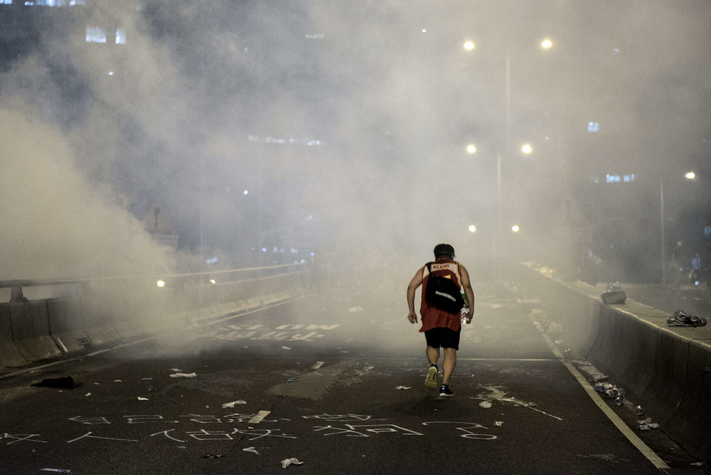. A pro-democracy protester runs along a road after the police fired tear gas in Hong Kong on September 28, 2014. Police fired tear gas as tens of thousands of pro-democracy demonstrators brought parts of central Hong Kong to a standstill on September 28, in a dramatic escalation of protests that have gripped the semi-autonomous Chinese city for days. It marked a dramatic escalation of protests in the city, which rarely sees such violence, after a tense week of largely contained student-led demonstrations exploded into mass angry street protests.  AFP PHOTO / ALEX OGLEAlex Ogle/AFP/Getty Images