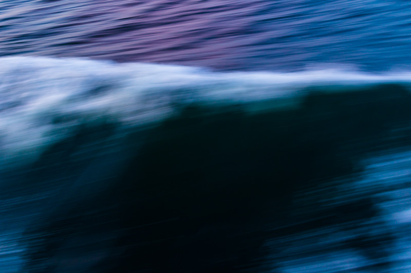 The edge of a wave is caught in an abstract pattern against the sea
