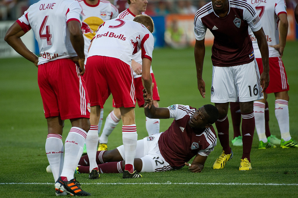 . DENVER - JULY 4: Hendry Thomas, #12 of the Colorado Rapids, looks up for a hand from Markus Holgersson, #5 of the New York Red Bulls, after Holgersson tripped Thomas during the first half of a MLS soccer match against the New York Red Bulls on July 4, 2013 at Dick\'s Sporting Goods Park. (Photo By Grant Hindsley / The Denver Post)