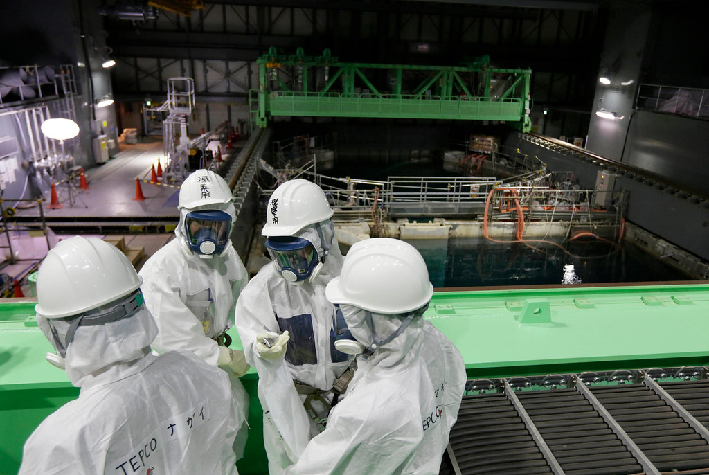 . Tokyo Electric Power Co. (TEPCO) employees and journalists wearing protective suits and masks look at the spent fuel pool inside the building housing the Unit 4 reactor at the Fukushima Dai-ichi nuclear power plant in Okuma town, Fukushima prefecture, northeastern Japan, Thursday, Nov. 7, 2013.  (AP Photo/Kimimasa Mayama, Pool)