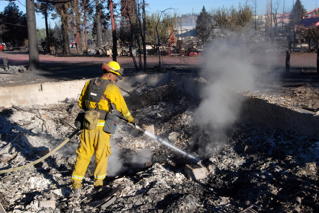 . A firefighter hoses down smoking rubble, Tuesday, Sept. 16, 2014, inside the foundation of a home destoyed by a wildfire in Weed, Calif.  (AP Photo/Jeff Barnard)