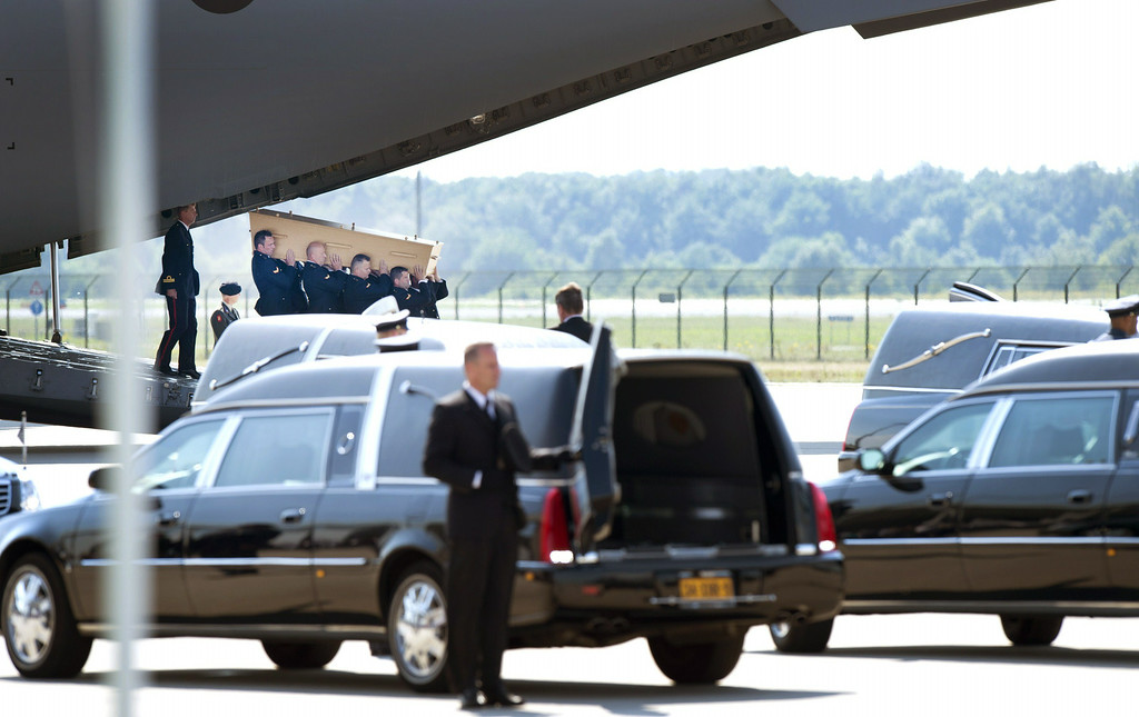 . Dutch military men carry a coffin after a Hercules transport aircraft of the Royal Dutch Airforce, carrying bodies from downed Malaysia Airlines flight MH17, landed from Kharkiv at Eindhoven Airbase on July 23, 2014. The first bodies from flight MH17 arrived in the Netherlands on Wednesday almost a week after it was shot down over Ukraine, with grieving relatives and the king and queen solemnly receiving the as yet unidentified victims. AFP PHOTO / ANP / MARCEL VAN HOORN/AFP/Getty Images
