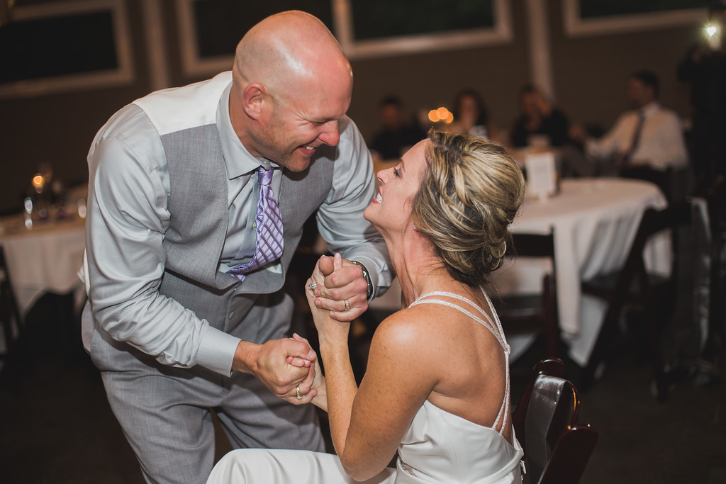 bride and groom embrace after garter toss