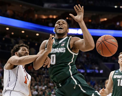 . Michigan State\'s Marvin Clark Jr. (0) is fouled by Virginia\'s Anthony Gill, left, during the first half of an NCAA tournament college basketball game in the Round of 32 in Charlotte, N.C., Sunday, March 22, 2015. (AP Photo/Gerald Herbert)