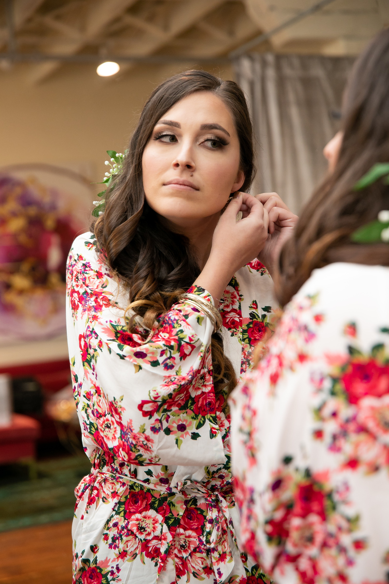 a bride putting on her earrings just before her wedding as she wears a white and floral japanese-style robe