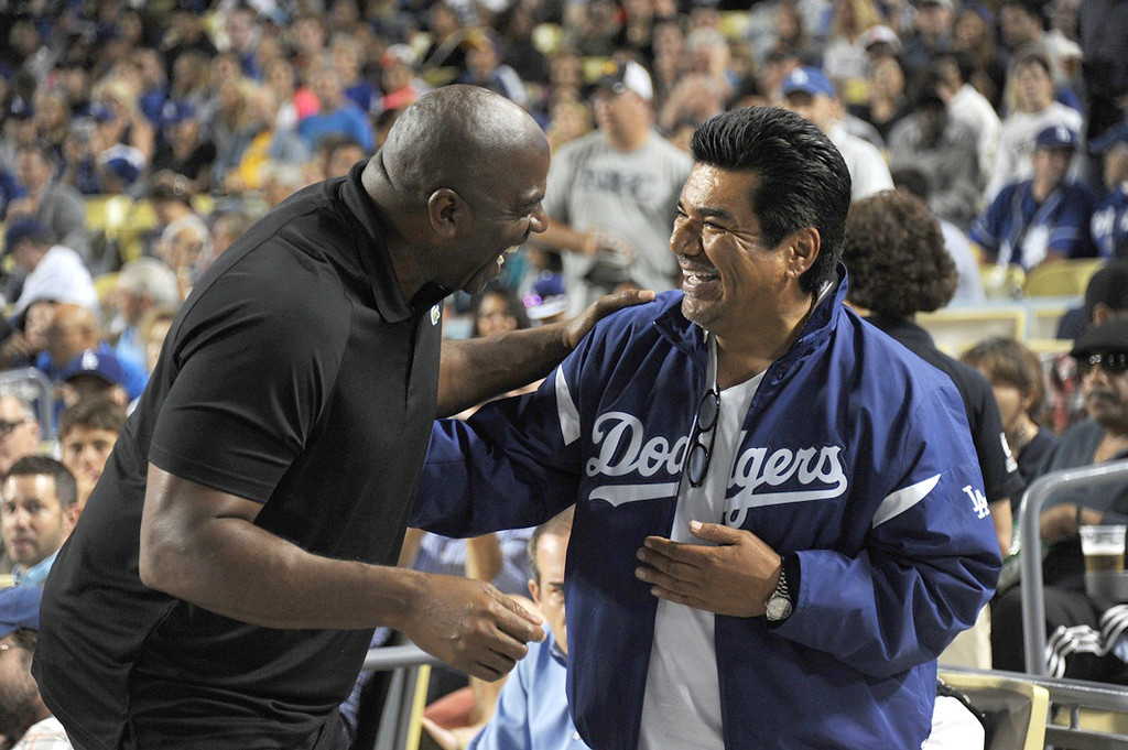 . In this handout photo provided by the Los Angeles Dodgers, Magic Johnson and George Lopez attend the Cincinnatti Reds versus Los Angeles Dodgers game at Dodger Stadium on July 26, 2013 in Los Angeles, California.  (Photo by Jon Soohoo/Los Angeles Dodgers via Getty Images)