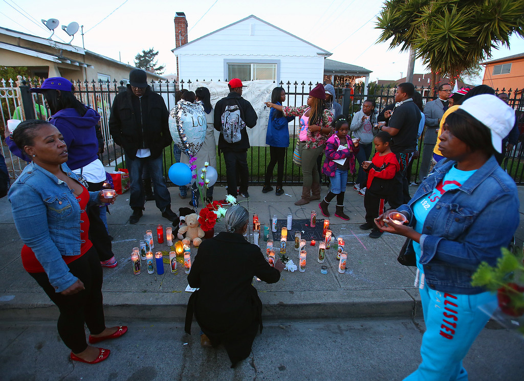 . Community members take part in a vigil for Lee Weathersby III onThursday, Jan. 2, 2014 in Oakland, Calif.  Weathersby,13, was shot and killed while coming home from the Boys and Girls Club on New Year\'s Eve.  (Aric Crabb/Bay Area News Group)