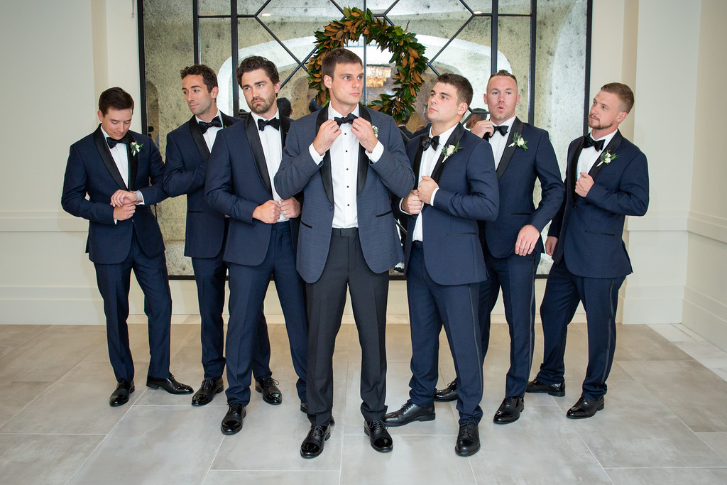 groomsmen wearing blue textured tuxedos posing around the groom