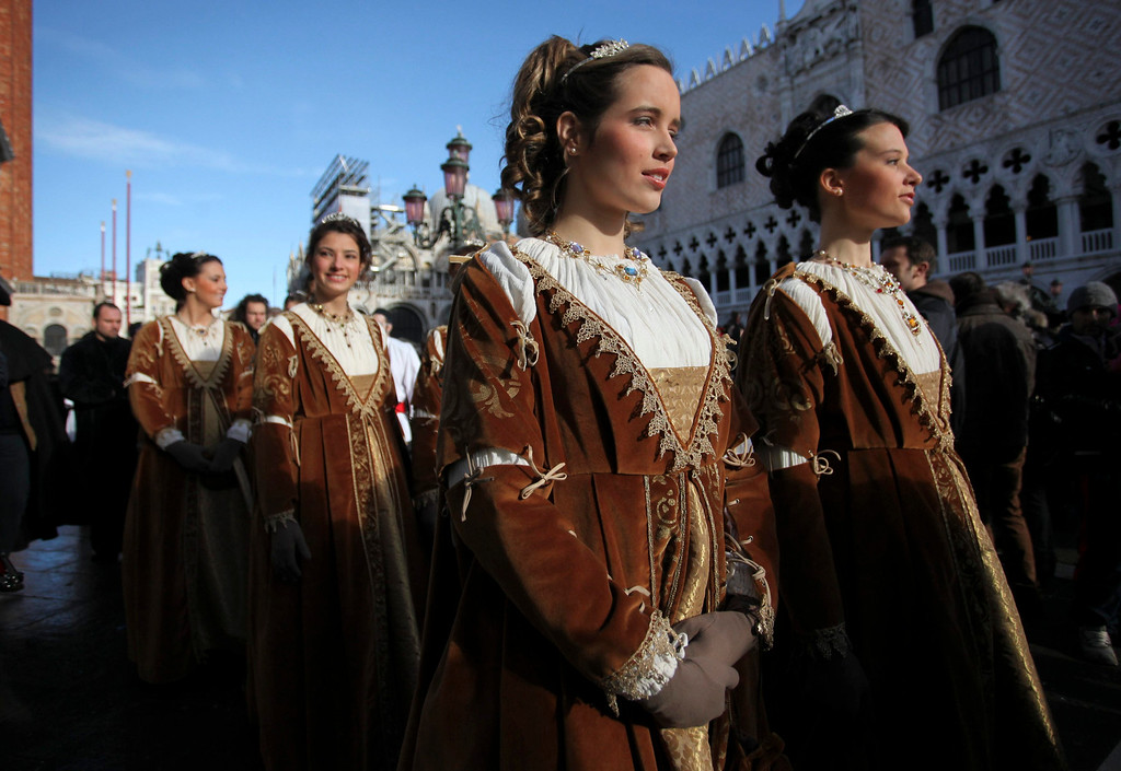 . Women dressed in traditional costumes pose during the Venetian Carnival in Saint Mark\'s square in Venice February 3, 2013.  REUTERS/Manuel Silvestri