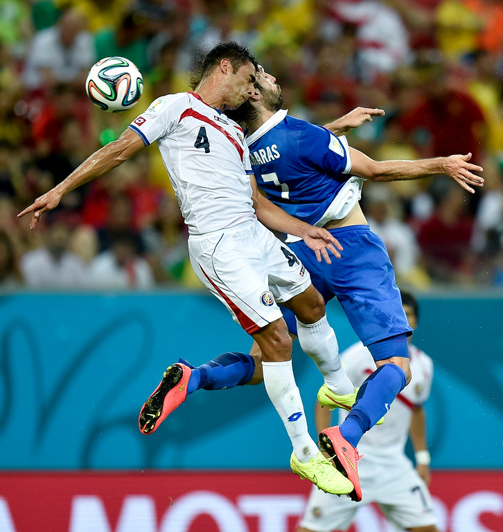 . Costa Rica\'s Michael Umana, left, heads the ball against Greece\'s Giorgos Samaras during the World Cup round of 16 soccer match between Costa Rica and Greece at the Arena Pernambuco in Recife, Brazil, Sunday, June 29, 2014. (AP Photo/Martin Meissner)