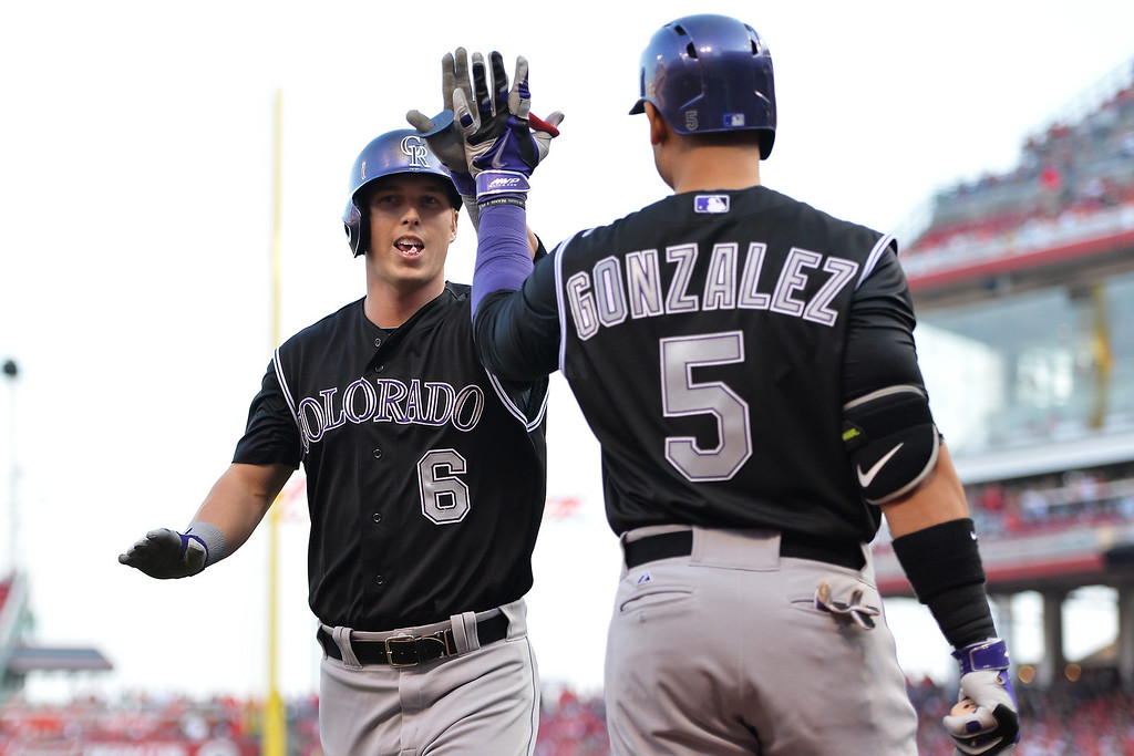 . CINCINNATI, OH - MAY 10:  Corey Dickerson #6 of the Colorado Rockies celebrates his first inning solo home run against the Cincinnati Reds with teammate Carlos Gonzalez #5 of the Colorado Rockies at Great American Ball Park on May 10, 2014 in Cincinnati, Ohio.  (Photo by Jamie Sabau/Getty Images)