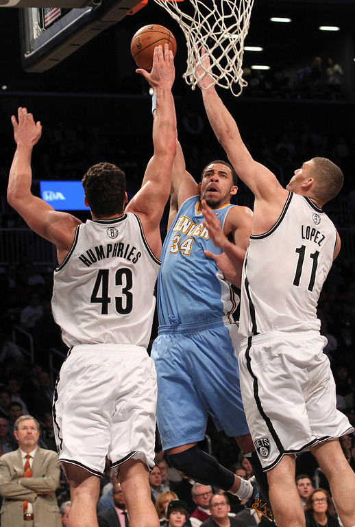 . Denver Nuggets\' JaVale McGee (34) goes up against Brooklyn Nets\' Kris Humphries and Brook Lopez during the second half of an NBA basketball game on Wednesday, Feb. 13, 2013, at Barclays Center in New York. The Nuggets won 119-108. (AP Photo/Mary Altaffer)