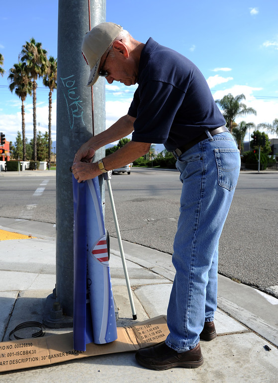 . (John Valenzuela/Staff Photographer) Redlands Evening Kiwanis Club member Gary Cross get ready to send up a Hometown Heroes banner of Redlands\' Naval officer Samantha Kelly at the corner of New Jersey St. and Redlands Blvd., Tuesday, August 27, 2013. Kelly is a 2006 Redlands East Valley grad.
