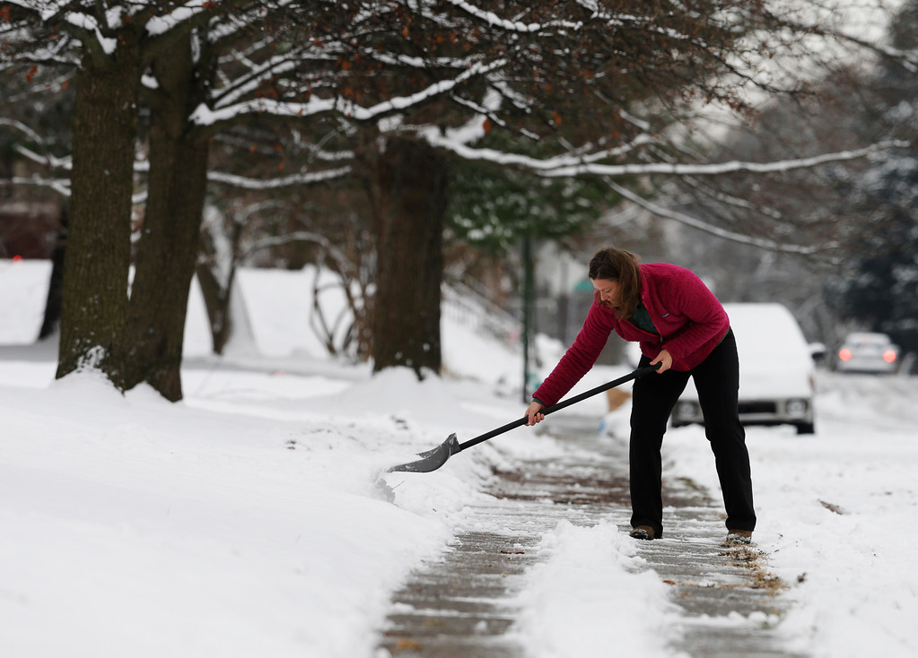 . Amy Davison shovels snow in her neighborhood following a winter storm Friday, Dec. 6, 2013, in Indianapolis. Several inches of snow fell on central and southern Indiana, making driving treacherous and leading to at least two fatal crashes. (AP Photo/Darron Cummings)